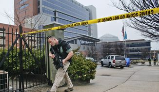 A law enforcement official makes his way around the perimeter outside the New Castle County Courthouse in Wilmington, Del., on Feb. 11, 2013, after three people in a shooting at the courthouse, including the gunman. (Associated Press)