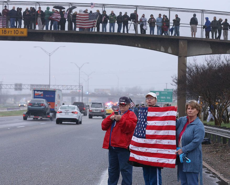 Supports of Chris Kyle in Midlothian, Texas, line up along the southbound lane of Interstate 35, Tuesday, Feb. 12, 2013, in Waco, Texas, for his final journey to Austin, where he will be buried at the Texas State Cemetery. Kyle and his friend Chad Littlefield were shot and killed Feb 2. at a North Texas gun range. (AP Photo/Waco Tribune Herald, Rod Aydelotte)