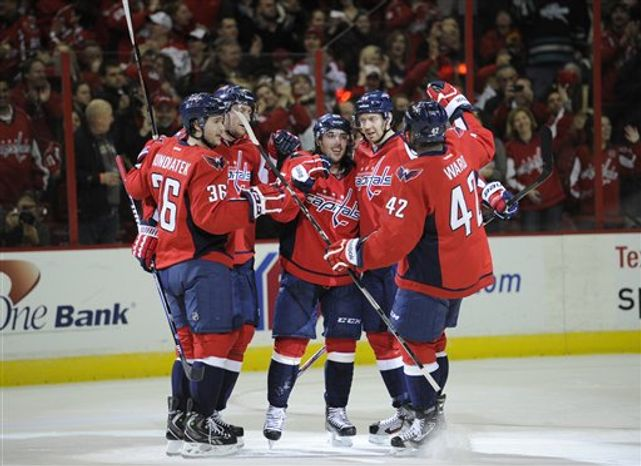 Washington Capitals center Mathieu Perreault, center, celebrates hi shoal with teammates including Tomas Kundratek (36), Joel Ward (42), and Eric Fehr, second from right, against the Florida Panthers during the third period of an NHL hockey game, Saturday, Feb. 9, 2013, in Washington. The Capitals won 5-0. (AP Photo/Nick Wass)