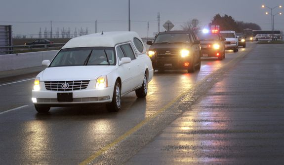 A hearse containing former Navy SEAL Chris Kyle's casket leads a motorcade leaving the Multi-Purpose Stadium in Midlothian, Texas, on Feb. 12, 2013 for the 200-mile journey to Austin, where Kyle will be buried at the Texas State Cemetery. Kyle and his friend Chad Littlefield were shot and killed Feb 2. at a North Texas gun range. (Associated Press/Star-Telegram)