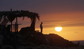 ** FILE** A Palestinian watches a sunset in Gaza City, Sunday, Feb. 10, 2013. (AP Photo/Hatem Moussa)
