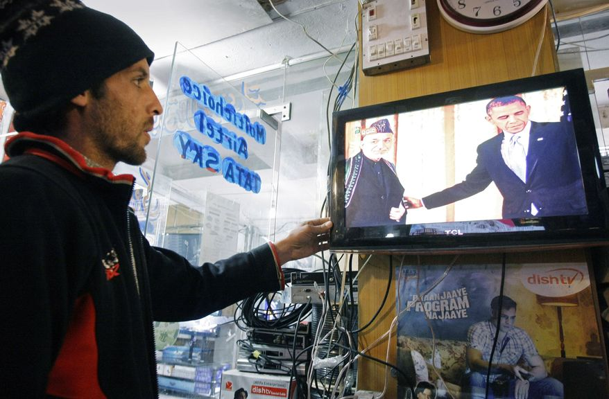 An Afghan searches channels to watch U.S. President Obama's State of Union address on a television news report in Kabul, Afghanistan, on Wednesday, Feb. 13, 2013. (AP Photo/Musadeq Sadeq)