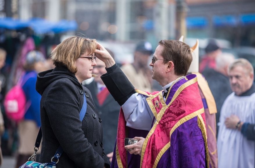 Father Nathan Humphrey smears ash in the form of a cross on a commuter's forehead in celebration of Ash Wednesday, a Catholic tradition, next to the Foggy Bottom-GWU Metro station in D.C. on Feb. 13, 2013. (Andrew S. Geraci/The Washington Times)