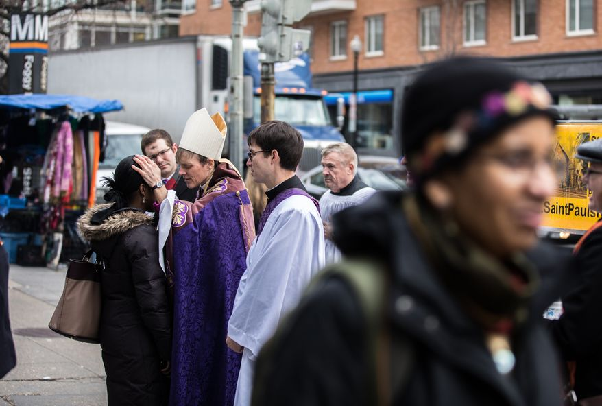 Bishop Mariann Edgar Budde of the Washington Episcopal Diocese smears ash in the form of a cross on the forehead of Sandrine Rukundo in celebration of Ash Wednesday, a Catholic tradition, next to the Foggy Bottom-GWU Metro station in D.C. on Feb. 13, 2013. (Andrew S. Geraci/The Washington Times)