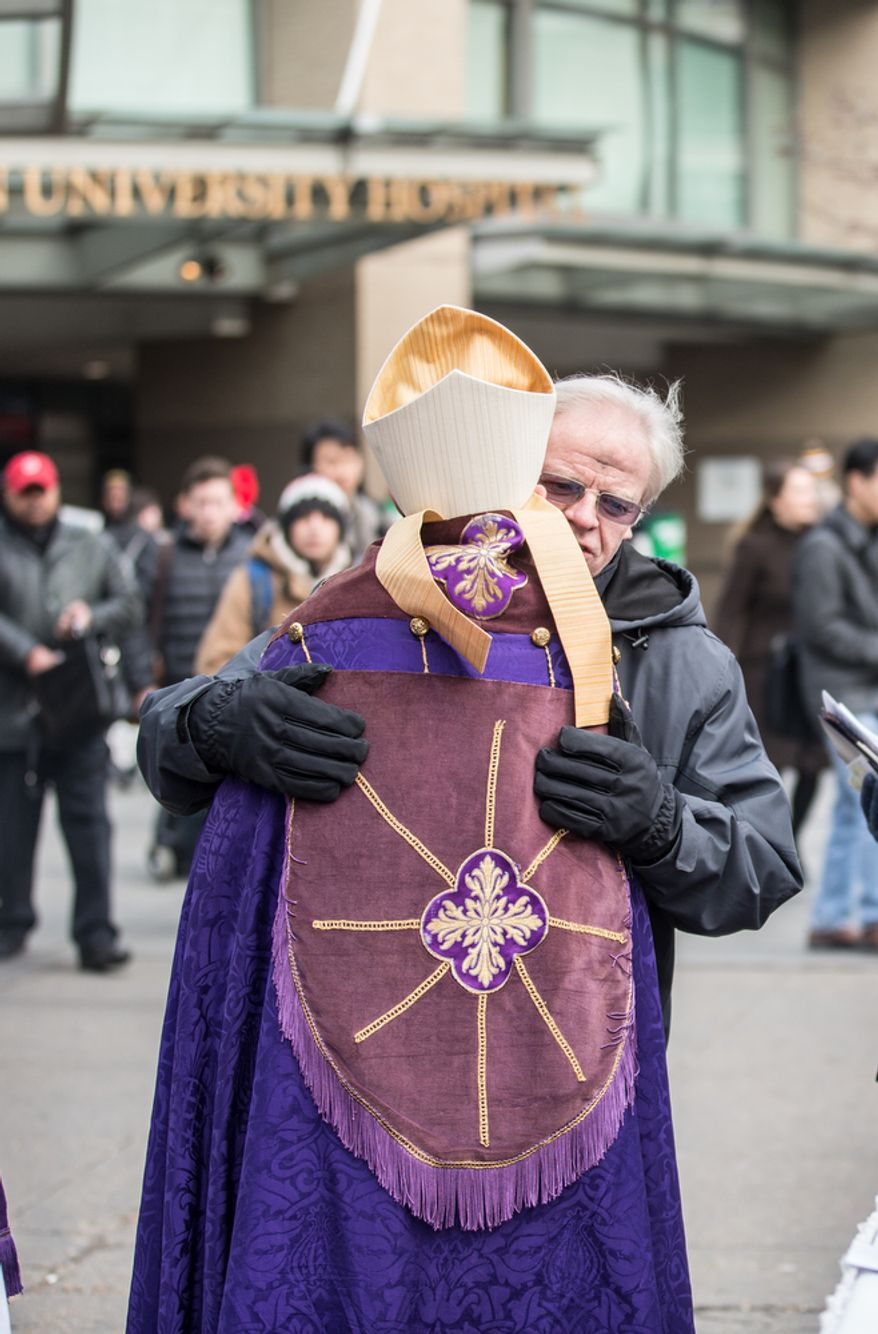 Bishop Mariann Edgar Budde of the Washington Episcopal Diocese hugs a commuter after placing ash on his forehead in celebration of Ash Wednesday, a Catholic tradition, next to the Foggy Bottom-GWU Metro station in D.C. on Feb. 13, 2013. (Andrew S. Geraci/The Washington Times)