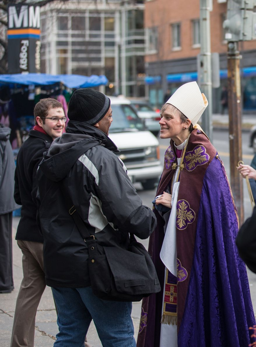 Bishop Mariann Edgar Budde of the Washington Episcopal Diocese greets a commuter before placing ash on his forehead in celebration of Ash Wednesday, a Catholic tradition, next to the Foggy Bottom-GWU Metro station in D.C. on Feb. 13, 2013. (Andrew S. Geraci/The Washington Times)