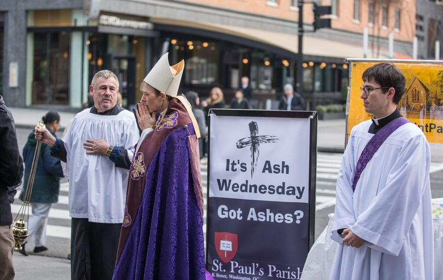 Bishop Mariann Edgar Budde of the Washington Episcopal Diocese warms her hands as she waits to place ash on the forehead of daily commuters to celebrate Ash Wednesday, a Catholic tradition, next to the Foggy Bottom-GWU Metro station in D.C. on Feb. 13, 2013. (Andrew S. Geraci/The Washington Times)