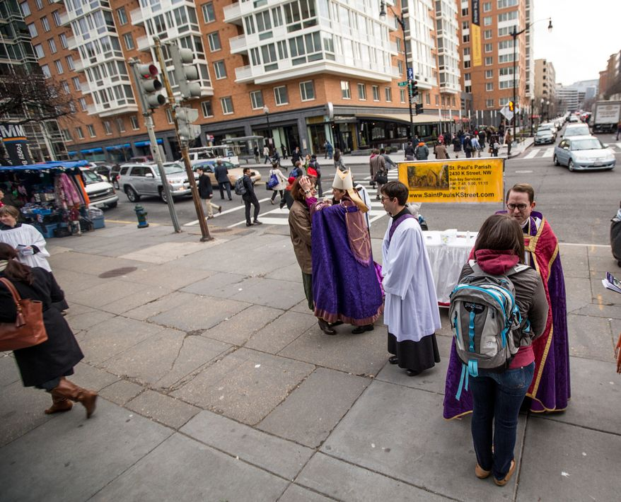 Bishop Mariann Edgar Budde of the Washington Episcopal Diocese and Father Nathan Humphrey place ash on the foreheads of morning commuters to celebrate Ash Wednesday, a Catholic tradition, next to the Foggy Bottom-GWU Metro station in D.C. on Feb. 13, 2013. (Andrew S. Geraci/The Washington Times)