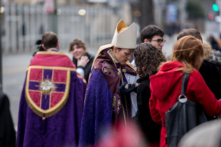 Bishop Mariann Edgar Budde of the Washington Episcopal Diocese bows her head and says a prayer after placing ash on a commuter's forehead in celebration of Ash Wednesday, a Catholic tradition, next to the Foggy Bottom-GWU Metro station in D.C. on Feb. 13, 2013. (Andrew S. Geraci/The Washington Times)
