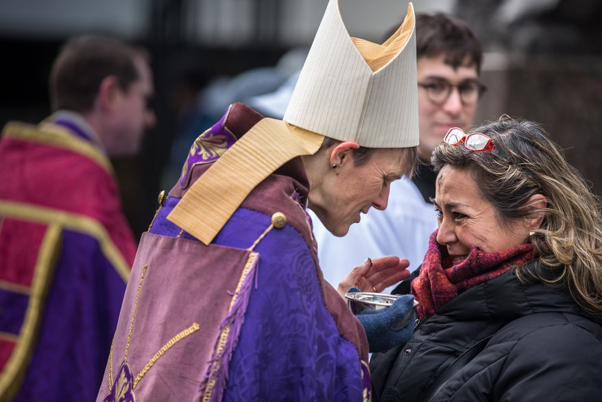 Grecilea Lopz of Washington receives ash and a blessing from Bishop Mariann Edgar Budde of the Washington Episcopal Diocese in celebration of Ash Wednesday, a Catholic tradition, next to the Foggy Bottom-GWU Metro station in D.C. on Feb. 13, 2013. (Andrew S. Geraci/The Washington Times)