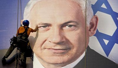 ** FILE ** In this Thursday, Jan. 17, 2013, file photograph, a worker hangs a huge poster with an image of Israel's Prime Minister Benjamin Netanyahu overlooking the Ayalon freeway in Tel Aviv, Israel. (AP Photo/Ariel Schalit, File)