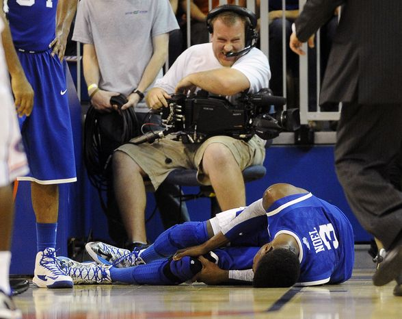 A cameraman grimaces after a collision with Kentucky forward Nerlens Noel (3) during the second half of an NCAA college basketball game against Florida in Gainesville, Fla., Tuesday, Feb. 12, 2013. Noel injured his left knee and did not return. Florida won 69-52. (AP Photo/Phil Sandlin)