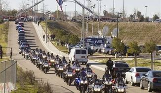 Police patrol cars and motorcycles escort the hearse containing the casket of Riverside Officer Michael Crain outside the Grove Community Church in Riverside, Calif., Wednesday, Feb. 13. The 34-year-old Crain was ambushed in his patrol car on Feb. 7. Authorities believe the shooter was ex-Los Angeles policeman Christopher Dorner. (Associated Press)