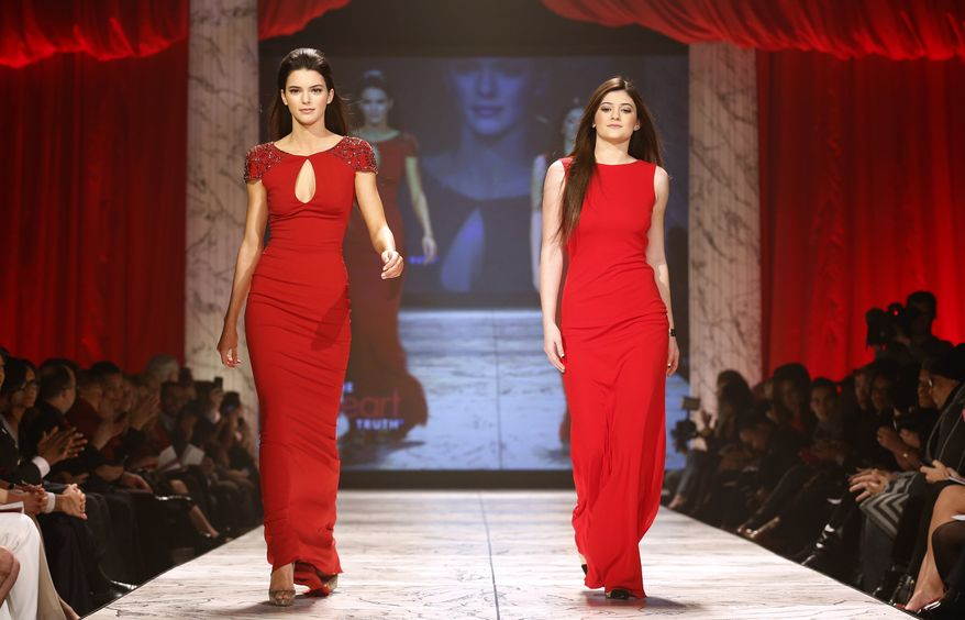 Kendall Jenner (left) and Kylie Jenner walk the runway at the Red Dress Collection 2013 Fashion Show in New York on Wednesday, Feb. 6, 2013. (John Minchillo/Invision/AP)