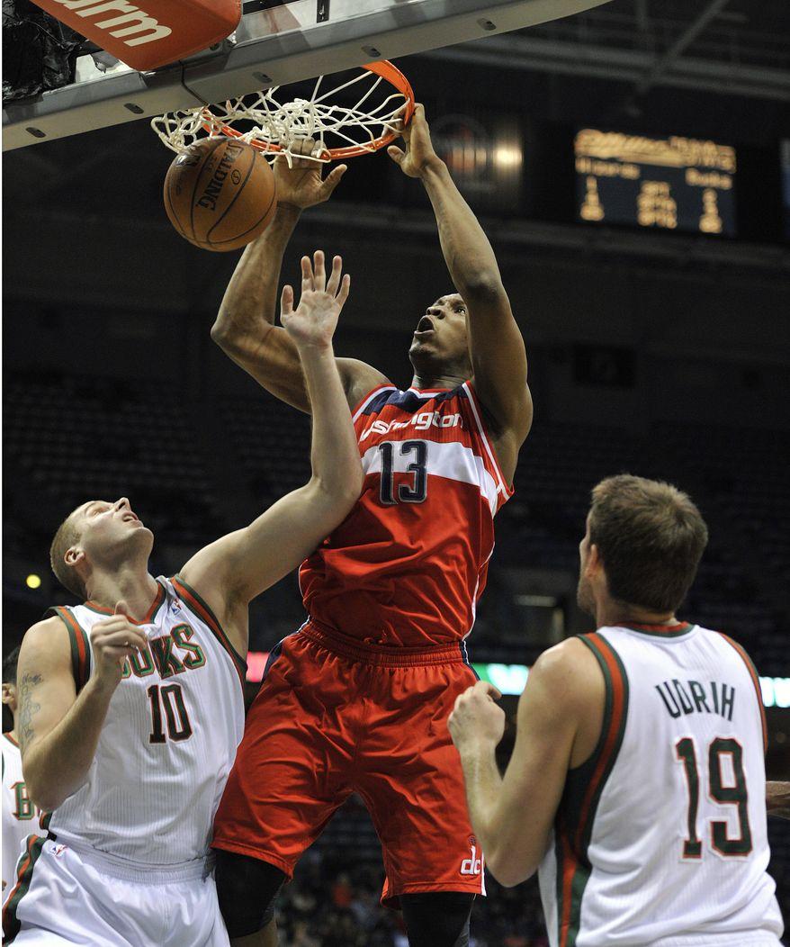 Washington Wizards' Kevin Seraphin (13) dunks the ball between Milwaukee Bucks' Joel Przybilla (10) and Beno Udrih (19) during the first half of an NBA basketball game Monday, Feb. 11, 2013, in Milwaukee. (AP Photo/Jim Prisching)