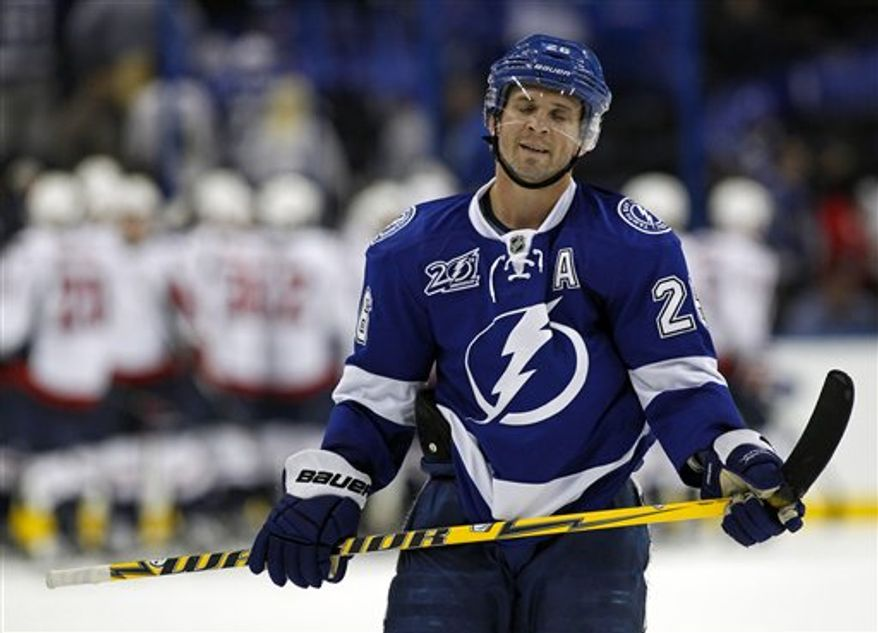 Tampa Bay Lightning's Martin St. Louis reacts at the end of an NHL hockey game as the Washington Capitals celebrate on Thursday, Feb. 14, 2013, in Tampa, Fla. The Capitals won 4-3. (AP Photo/Mike Carlson)