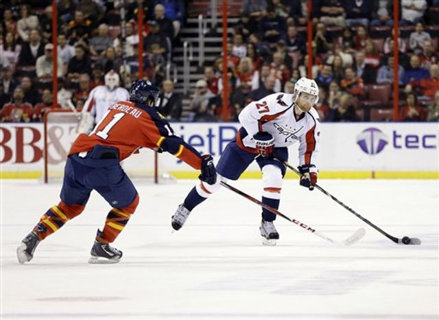 Washington Capitals defenseman Karl Alzner (27) passes past Florida Panthers center Jonathan Huberdeau (11) during the first period of an NHL hockey game, Tuesday, Feb. 12, 2013 in Sunrise, Fla. (AP Photo/Wilfredo Lee)