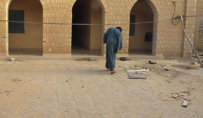 **FILE** Neighborhood resident Mohamed Alassane ducks under a wire Feb. 6, 2013, to enter the Ministry of Finance's Regional Audit Department in Timbuktu, Mali, a site used by al Qaeda-linked Islamists for more than a year. (Associated Press)