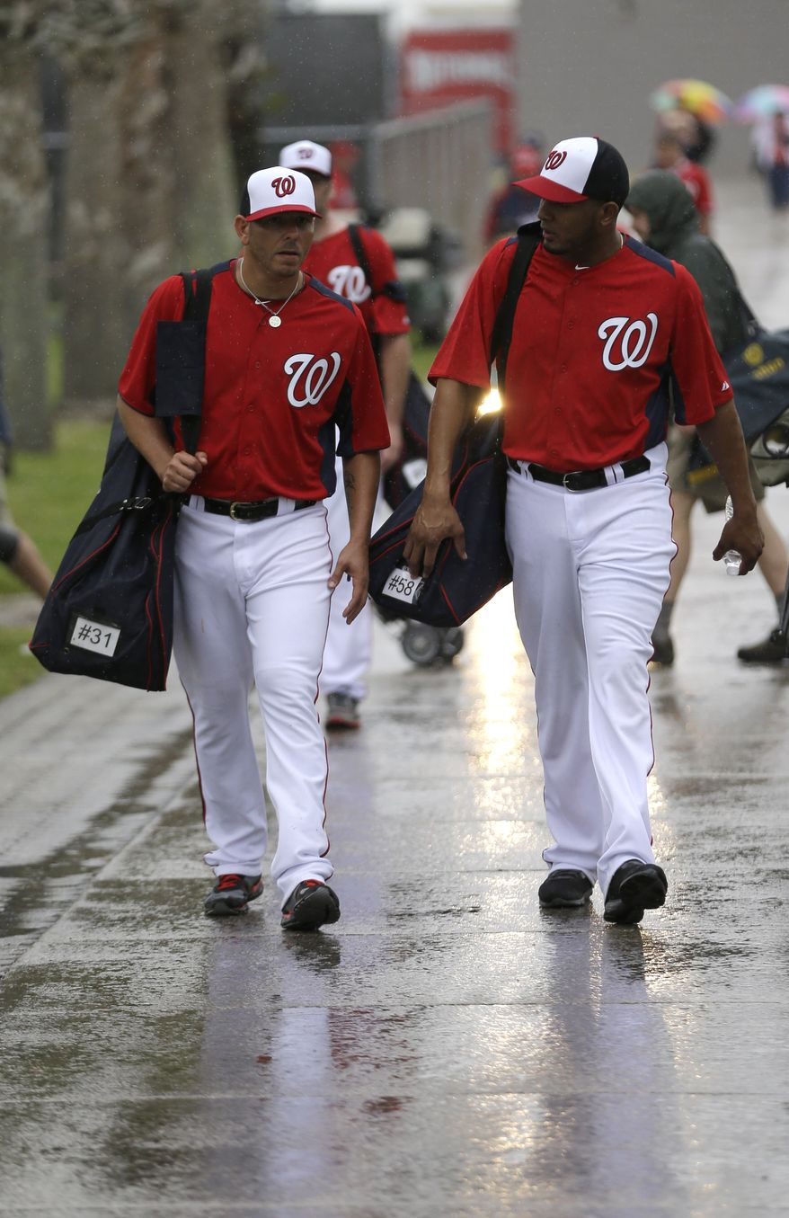 Washington Nationals pitchers Yunesky Maya, left, and Fernando Abad, right, leave the practice fields as rain falls after a spring training baseball workout Thursday, Feb. 14, 2013, in Viera, Fla. (AP Photo/David J. Phillip)