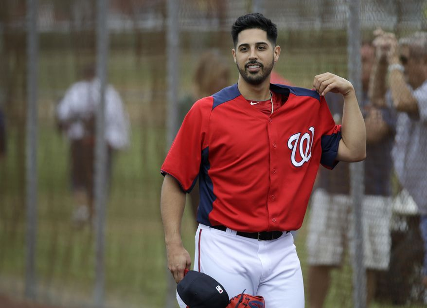 Washington Nationals pitcher Gio Gonzalez adjusts his jersey during a spring training baseball workout Thursday, Feb. 14, 2013, in Viera, Fla. (AP Photo/David J. Phillip)