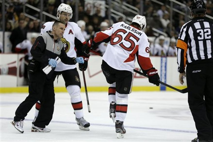 Ottawa Senators defenseman Erik Karlsson (65) limps off the ice as a team trainer arrives to help him after Karlsson collided with Pittsburgh Penguins left wing Matt Cooke during the second period of an NHL hockey game in Pittsburgh on Wednesday, Feb. 13, 2013. Karlsson did not return to the game. The Penguins won 4-2. (AP Photo/Gene J. Puskar)