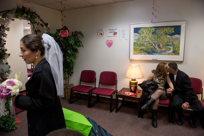 Ester Gales and Hanry Mauro Ramirez kiss in the waiting room after getting married on Valentine's Day as Justine Caccamo (left) of Washington, D.C., arrives before her wedding ceremony at the D.C. Superior Court building on Feb. 14, 2013. (Andrew Harnik/The Washington Times)