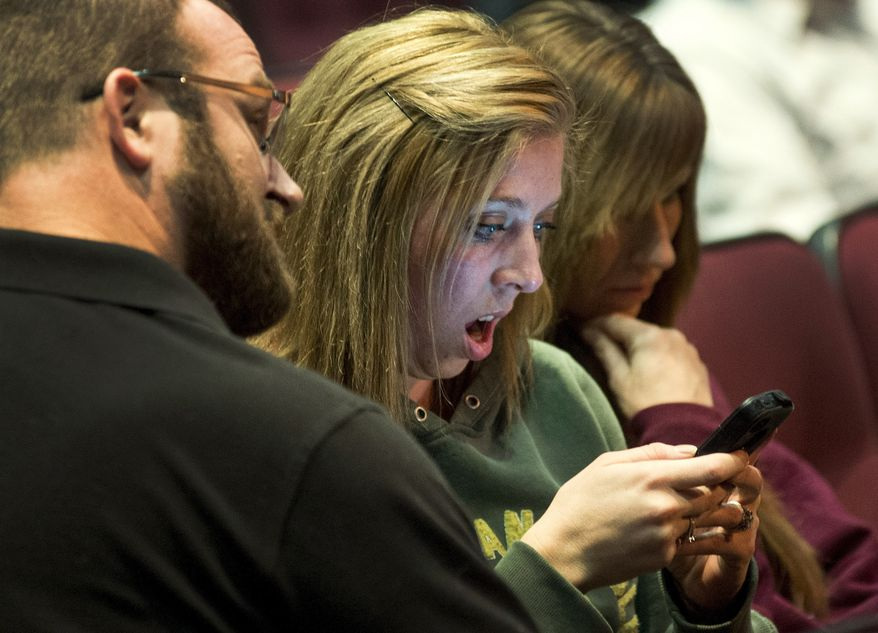 Parent Christy Gorst reacts while reading on her phone a news account detailing the plot by fifth-graders to kill classmates at Fort Colville Elementary School last week, Wednesday night, Feb. 13, 2013, during Colville Schools' Security Forum in Colville, Wash.  (AP Photo/The Spokesman-Review, Colin Mulvany)