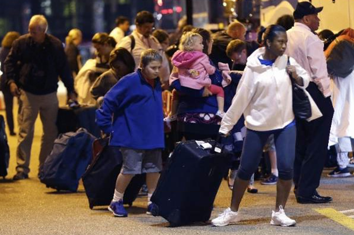 **FILE** Passengers from the disabled Carnival Triumph cruise ship arrive by bus at the Hilton Riverside Hotel in New Orleans on Friday, Feb. 15, 2013. The ship had been idled for nearly a week in the Gulf of Mexico following an engine-room fire. (AP Photo/Gerald Herbert)