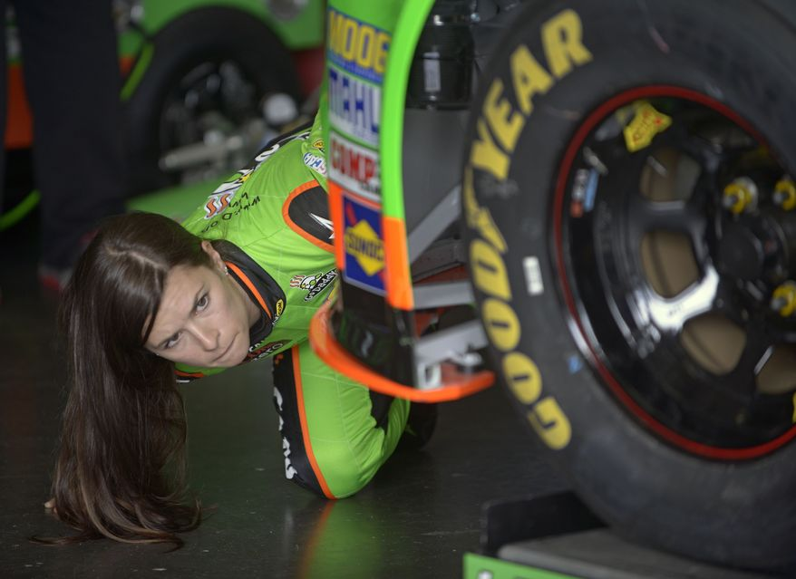 Danica Patrick checks out her car while crew members make adjustments in her garage during a practice session for the NASCAR Daytona 500 Sprint Cup Series auto race at Daytona International Speedway, Saturday, Feb. 16, 2013, in Daytona Beach, Fla. (AP Photo/Phelan M. Ebenhack)