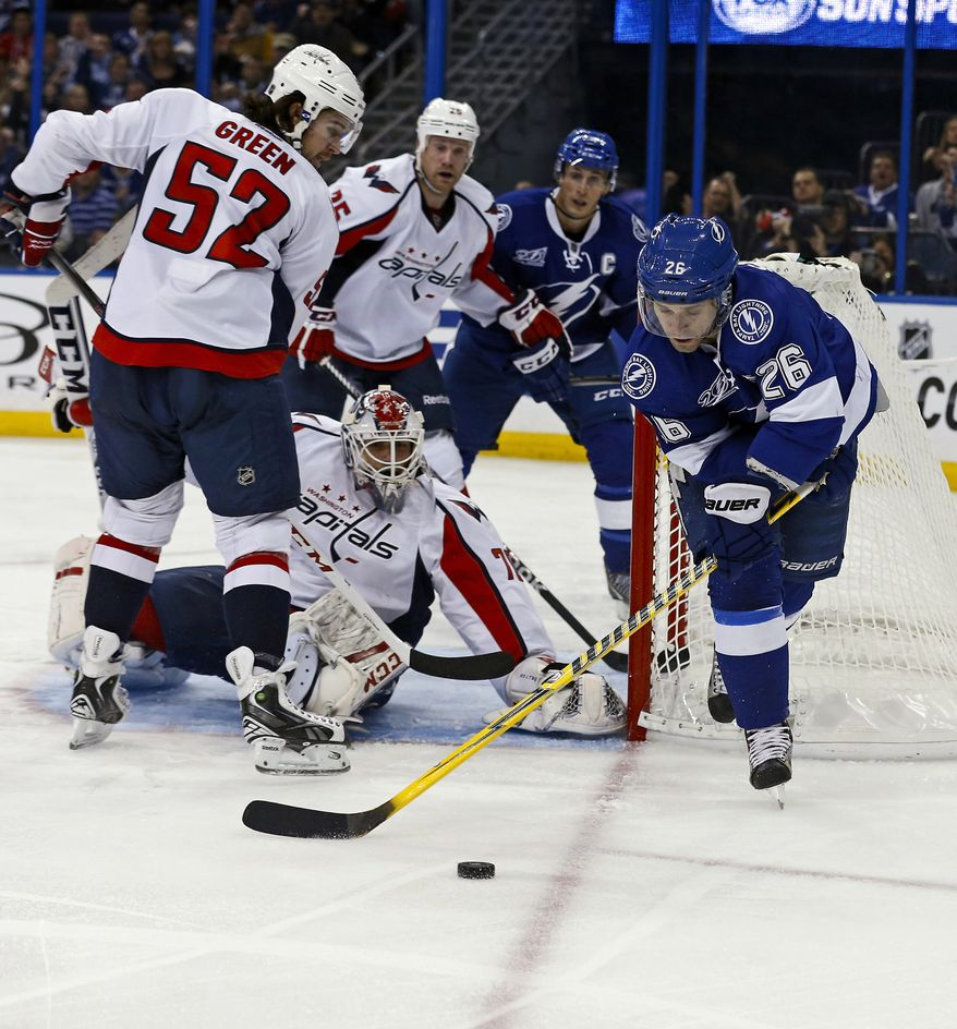 Tampa Bay Lightning's Martin St. Louis (26) tries to put back a rebound past Washington Capitals' Mike Green (52) and goalie Braden Holtby during the second period of an NHL hockey game on Thursday, Feb. 14, 2013, in Tampa, Fla. (AP Photo/Mike Carlson)