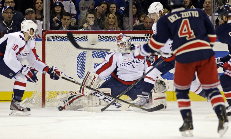 Washington Capitals goalie Braden Holtby, center, makes a save as New York Rangers defenseman Michael Del Zotto (4) watches in the first period of their NHL hockey game at Madison Square Garden in New York, Sunday, Feb. 17, 2013. Capitals right wing Eric Fehr, left, defends. The Rangers won 2-1. (AP Photo/Kathy Willens)