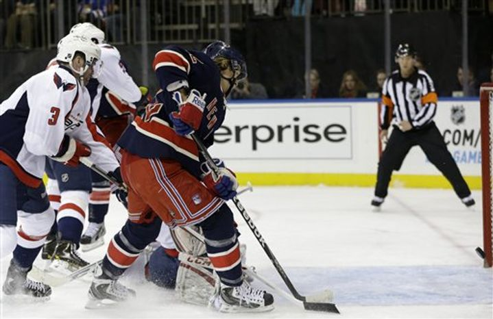 New York Rangers left wing Carl Hagelin, center, of Sweden, shoots a goal in the second period of their NHL hockey game against the Washington Capitals at Madison Square Garden in New York, Sunday, Feb. 17, 2013. Capitals defenseman Tom Poti (3) works against Hagelin. (AP Photo/Kathy Willens)