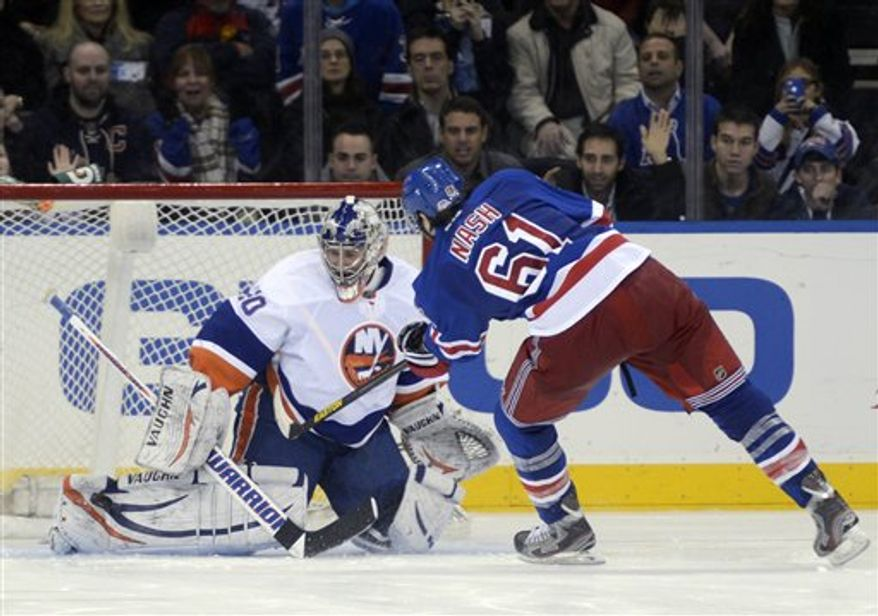 New York Islanders goalie Evgeni Nabokov, left, makes a save on a shot by New York Rangers' Rick Nash in the shootout of an NHL hockey game at Madison Square Garden in New York, Thursday, Feb. 14, 2013. The Islanders won 4-3. (AP Photo/Henny Ray Abrams)