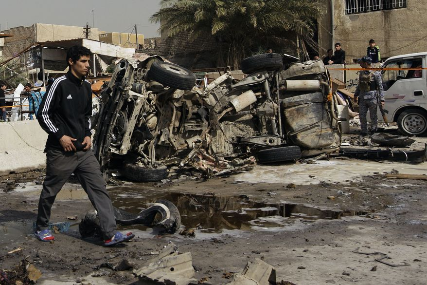 An Iraqi walks past the scene of a car bomb attack in the Ameen neighborhood of eastern Baghdad, on Sunday, Feb. 17, 2013. A series of car bombs exploded within minutes of one another as Iraqis were out shopping in and around the capital on Sunday, killing and wounding scores of people, police said. (AP Photo/Khalid Mohammed)