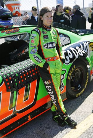 Danica Patrick stands by her car on pit road after qualifying for the NASCAR Daytona 500 Sprint Cup Series auto race at Daytona International Speedway, Sunday, Feb. 17, 2013, in Daytona Beach, Fla. Patrick won the pole, becoming the first woman to secure the top spot for any Sprint Cup race. (AP Photo/Terry Renna)