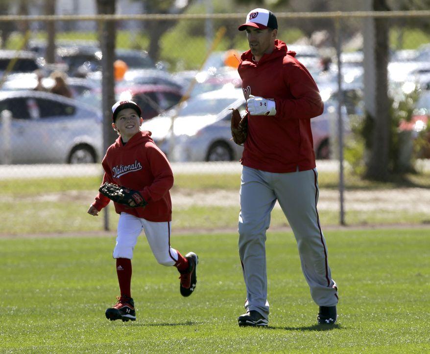 Washington Nationals first baseman Adam LaRoche, right, races his son Drake, left, during a spring training baseball workout on Sunday, Feb. 17, 2013, in Viera, Fla. (AP Photo/David J. Phillip)
