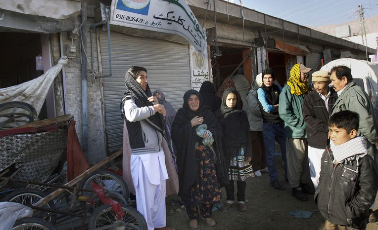 A Pakistani Shiite Muslim woman weeps on Sunday, Feb. 17, 2013, as she and other family member survey a market damaged in Saturday's deadly bombing in Quetta, Pakistan. (AP Photo/Arshad Butt)