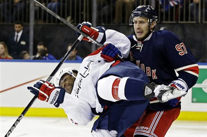 New York Rangers defenseman Matt Gilroy (97) checks Washington Capitals right wing Joel Ward (42) in the third period of their NHL hockey game at Madison Square Garden in New York, Sunday, Feb. 17, 2013. The Rangers won 2-1. (AP Photo/Kathy Willens)