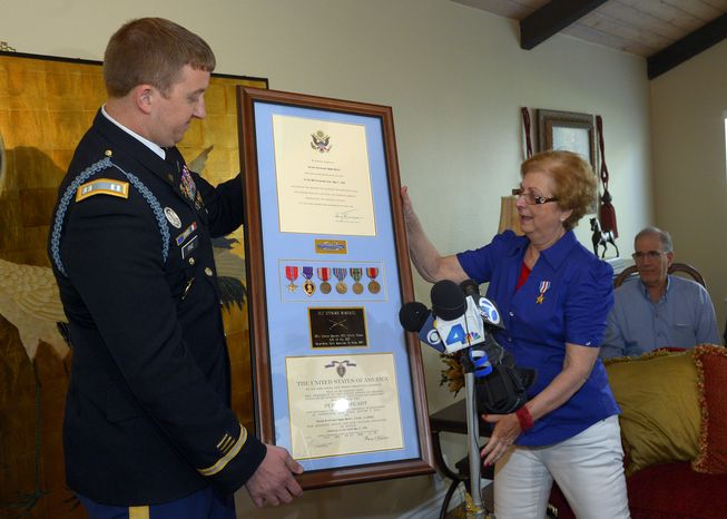 Army Capt. Zachariah L. Fike presents Hyla Merin with a plaque that contains (from left) the Bronze Star, the Purple Heart, the Army Good Conduct Medal, American Campaign Medal, European-African-Middle Eastern Campaign Medal and the World War II Victory Medal, along with a Silver Star that he pinned to her during a ceremony at her home in Thousand Oaks, Calif., on Feb. 17, 2013. The medals were presented posthumously to her father after they were recently discovered in an apartment where Merin's mother and aunts had once lived. (Associated Press)