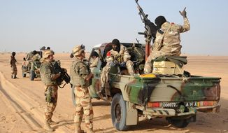 French troops talk with Malian soldiers outside Bourem, in northern Mali, on Sunday, Feb. 17, 2013. (AP Photo/Pascal Guyot, Pool)