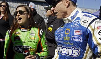 Mark Martin, right, and Danica Patrick laugh on pit road after their qualifying runs for the NASCAR Daytona 500 Sprint Cup Series auto race at Daytona International Speedway, Sunday, Feb. 17, 2013, in Daytona Beach, Fla. Patrick won the pole, becoming the first woman to secure the top spot for any Sprint Cup race. (AP Photo/John Raoux)