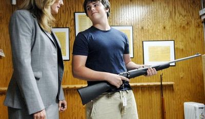 **FILE** Michael Steelman (right), 13, smiles at his mother, Missouri State Treasurer Sarah Steelman, after picking out a rifle while shopping at Ammo Alley in Hartsburg, Mo., on May 28, 2008. Steelman held a press conference to discuss her support of the 2nd Amendment to the U.S. Constitution before buying her son the rifle for his birthday. Ammo Alley owner J. Doug Alley helped the two pick out the Marlin 917S 17HMR model.