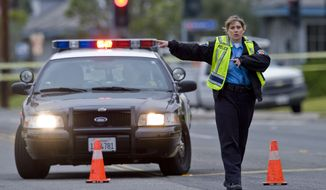 A police officer directs traffic as the investigation of a shooting spree in Orange County, Calif., continues on Tuesday, Feb. 19, 2013. (AP Photo/The Orange County Register, Mark Rightmire)