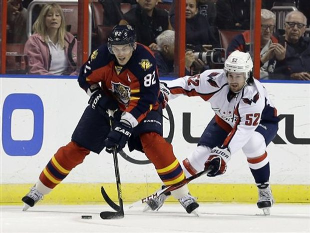 Florida Panthers center Tomas Kopecky (82) of Slovakia, and Washington Capitals defenseman Mike Green (52) of Canada, battle for the puck during the first period of an NHL hockey game, Tuesday, Feb. 12, 2013 in Sunrise, Fla. (AP Photo/Wilfredo Lee)