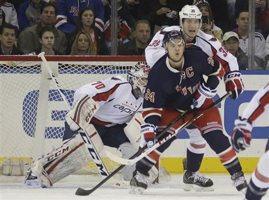 Washington Capitals goalie Braden Holtby (70) tries to get a view past Washington Capitals defenseman Tomas Kundratek (36) and New York Rangers right wing Ryan Callahan (24) in the first period of their NHL hockey game at Madison Square Garden in New York, Sunday, Feb. 17, 2013. (AP Photo/Kathy Willens)