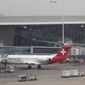 Baggage carts make their way past a Helvetic Airways aircraft from which millions' of dollars worth of diamonds were stolen on the tarmac of Brussels international airport, Tuesday, Feb. 19, 2013. (AP Photo/Yves Logghe)