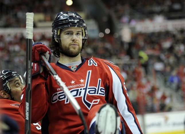 Washington Capitals defenseman Mike Green (52) looks on from the bench during the second period of an NHL hockey game against the Philadelphia Flyers, Friday, Feb. 1, 2013, in Washington. (AP Photo/Nick Wass)