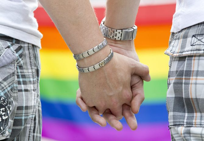 ** FILE ** Two gay men hold hands during Christopher Street Day celebrations in Weimar, Germany, on July 16, 2011. (AP Photo/dpa, Michael Reichel)