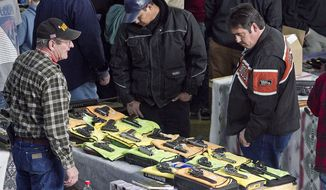 ** FILE ** People look at firearm displays at the Sports Connection Gun Show at the Modern Living Building at State Fair Park in Yakima, Wash., on Saturday, Feb. 16, 2013. (AP Photo/Yakima Herald-Republic, TJ Mullinax)