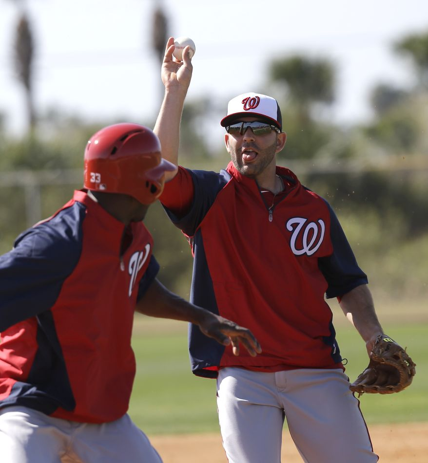 Washington Nationals infielder Danny Espinosa, right, tosses the ball as he chases Roger Bernadina (33) as part of a rundown drill during a spring training baseball workout Tuesday, Feb. 19, 2013, in Viera, Fla. (AP Photo/David J. Phillip)